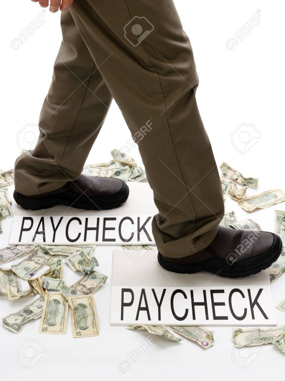 Person stepping from paycheck to paycheck with spent money lying crumpled on the ground. Stock Photo - 10878800