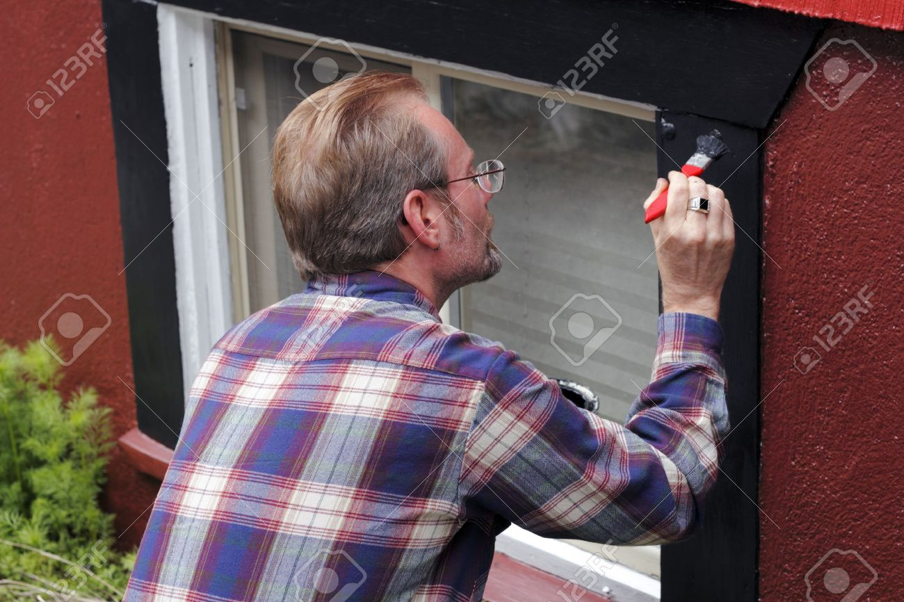 Man painting house window trim with black paint outdoors in the day. Stock Photo - 11110724