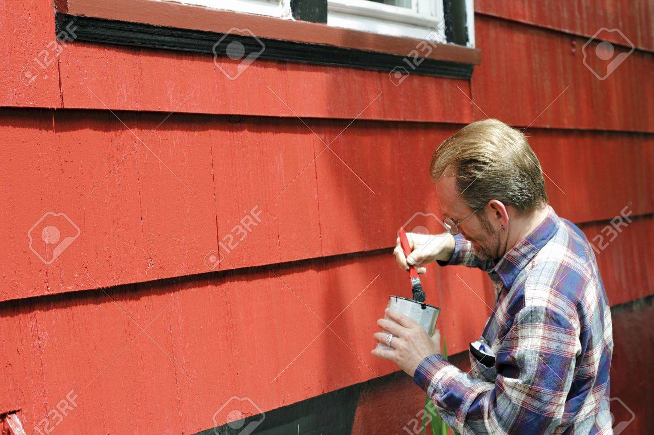 Mature male dipping a paintbrush in a can of black paint in order to touch up trim around the windows of his house on a sunny day. Stock Photo - 11110733