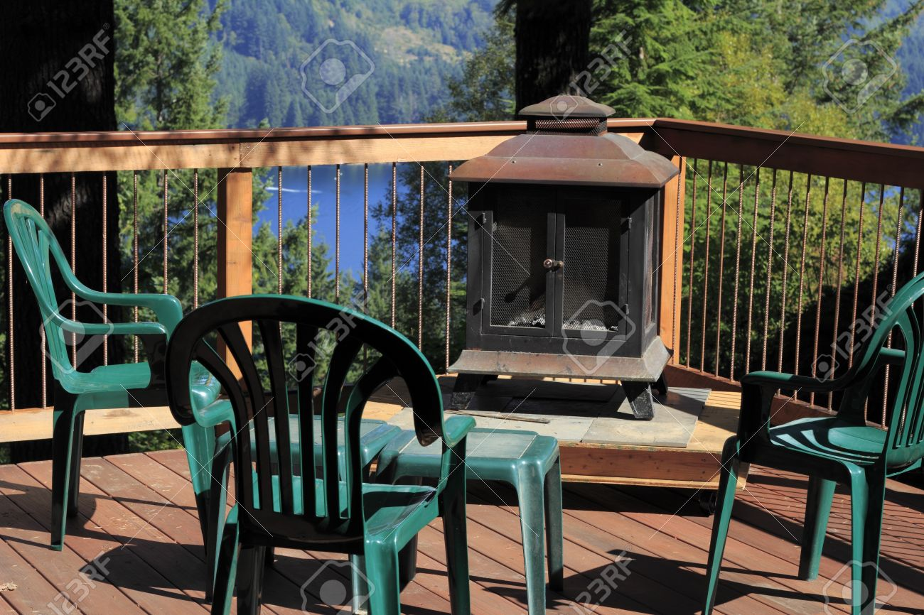 Four Plastic Chairs On A Scenic Sunny Outdoor Deck With A ...