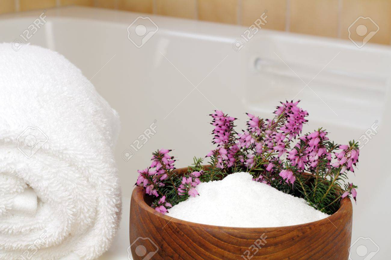 Fresh pink purple heather flowers in a teak wood bowl with epsom salts on the edge of a bathtub with a rolled up white towel ready to take a relaxing bath. Stock Photo - 11186670