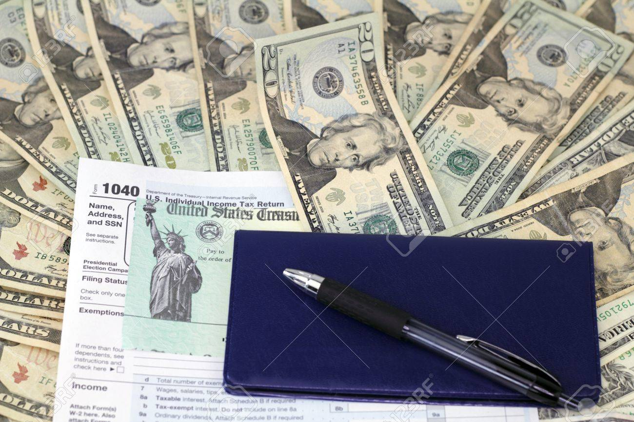 Pen and checkbook on top of tax refund check on a 1040 tax form on lots of paper cash ready to be deposited. Stock Photo - 11646002