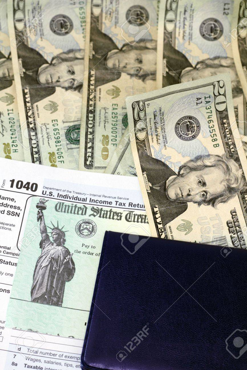 Checkbook on top of tax refund check and 1040 tax form on lots of paper cash ready to be deposited. Stock Photo - 11646003