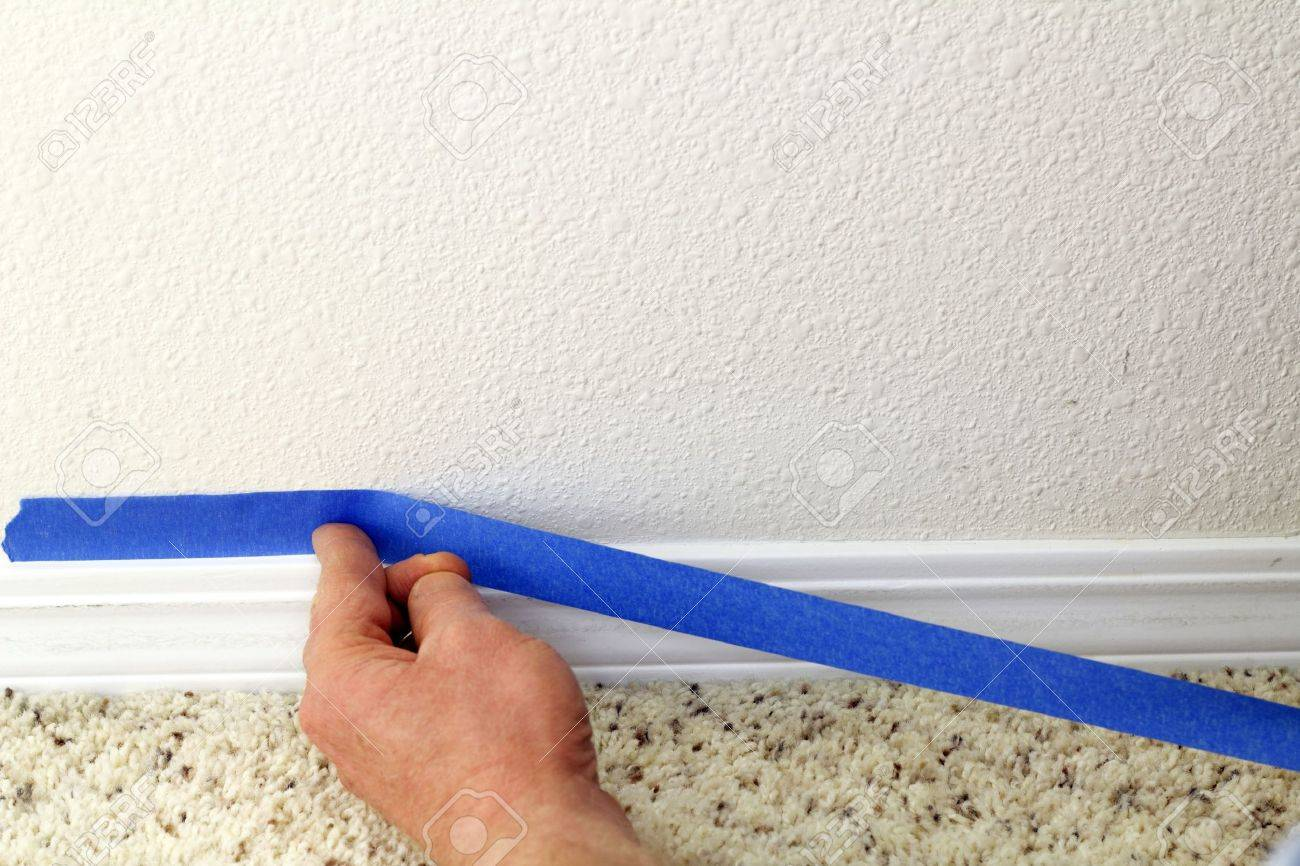 Male hand preparing to paint wall trim by placing blue painter Stock Photo - 12394010