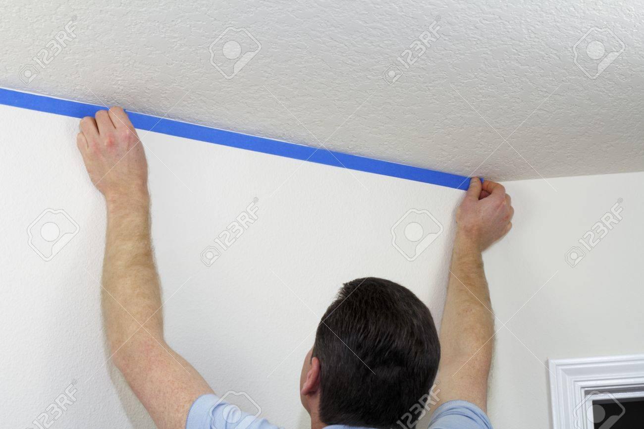 L Homme S Apprêtait à Peindre Au Plafond En Masquant Le Mur En Dessous Avec Le Peintre Bleu