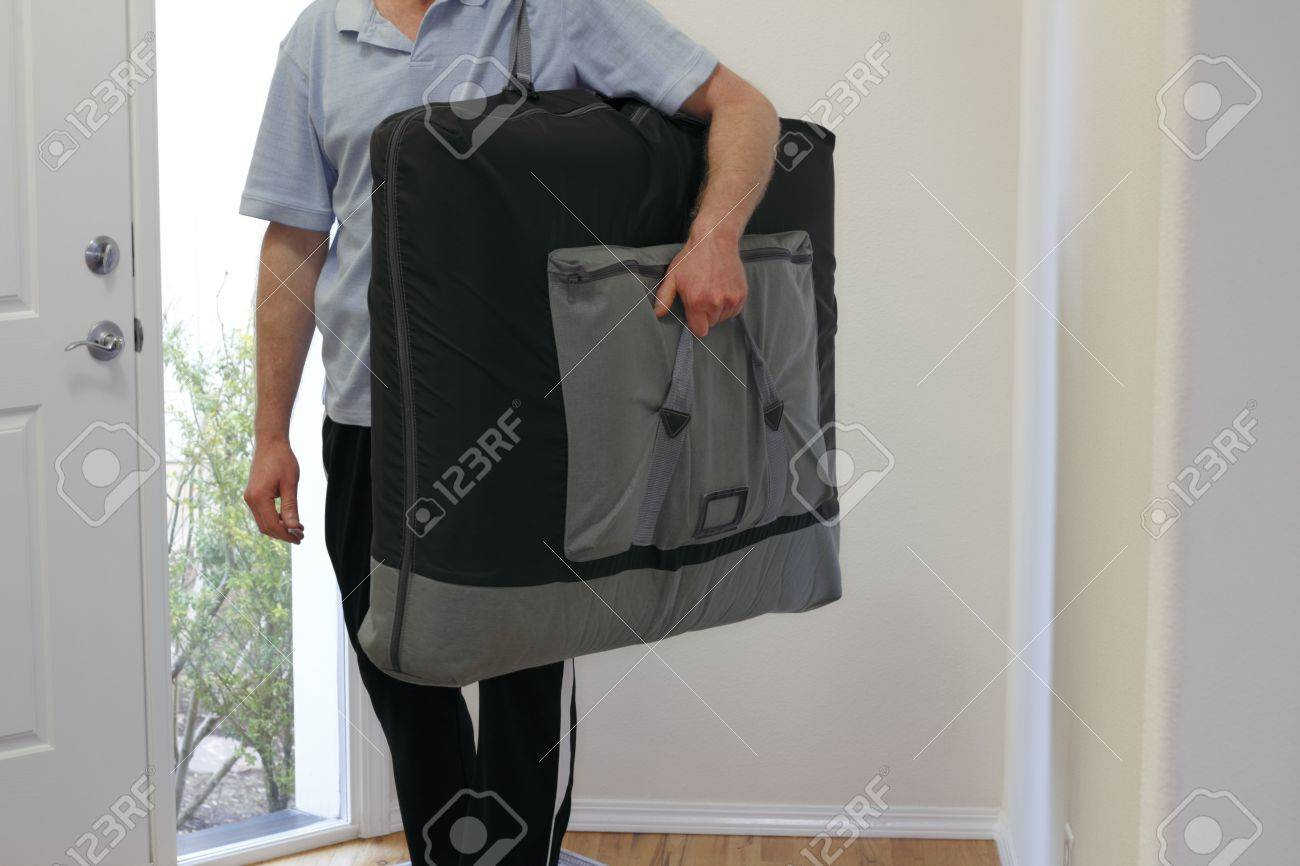 Standing inside the front door of a home a massage therapist is ready to set up the massage table he is carrying and massage his client. Stock Photo - 12391052