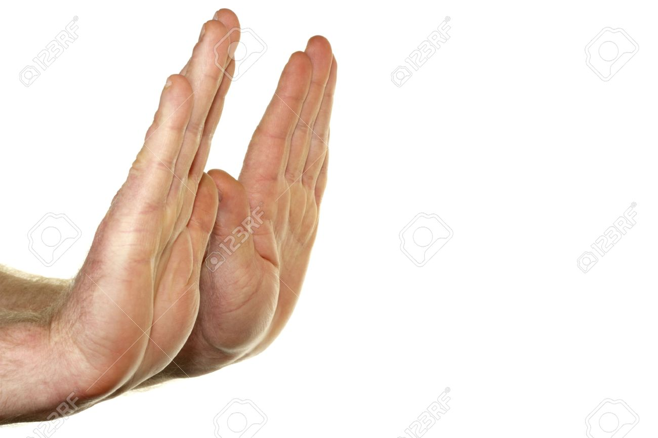 Adult male hands seen from the side with palms raised up in a stop gesture in front of a white background. Stock Photo - 12391044