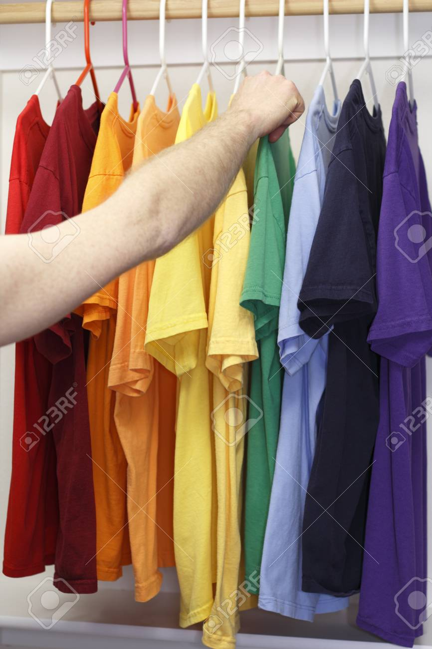 Arm and hand of a caucasian man seen choosing a t-shirt from a variety of shirts in a rainbow of colors in a closet. Stock Photo - 12393925