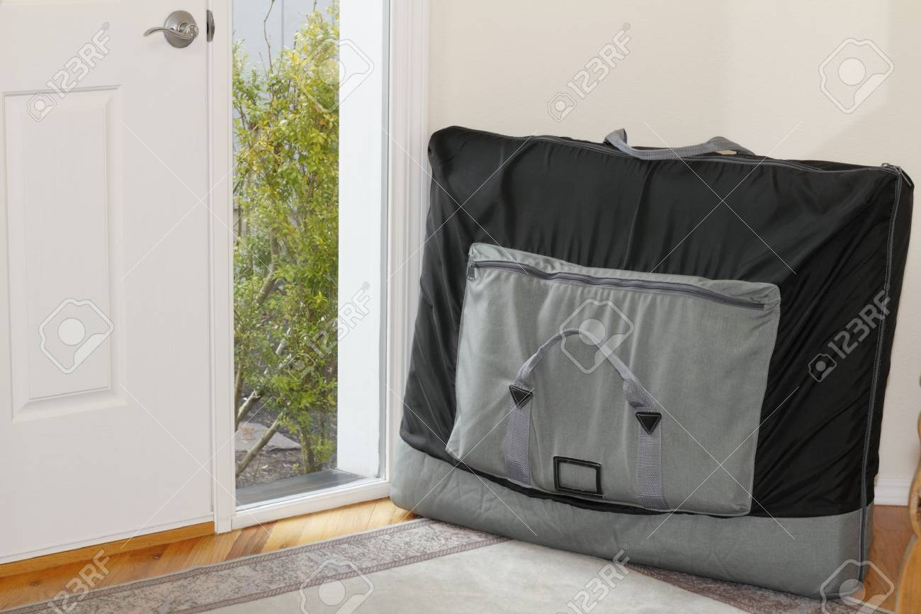 Outcall massage table in a black nylon carrying case leaning against an interior home foyer wall. Stock Photo - 12394021