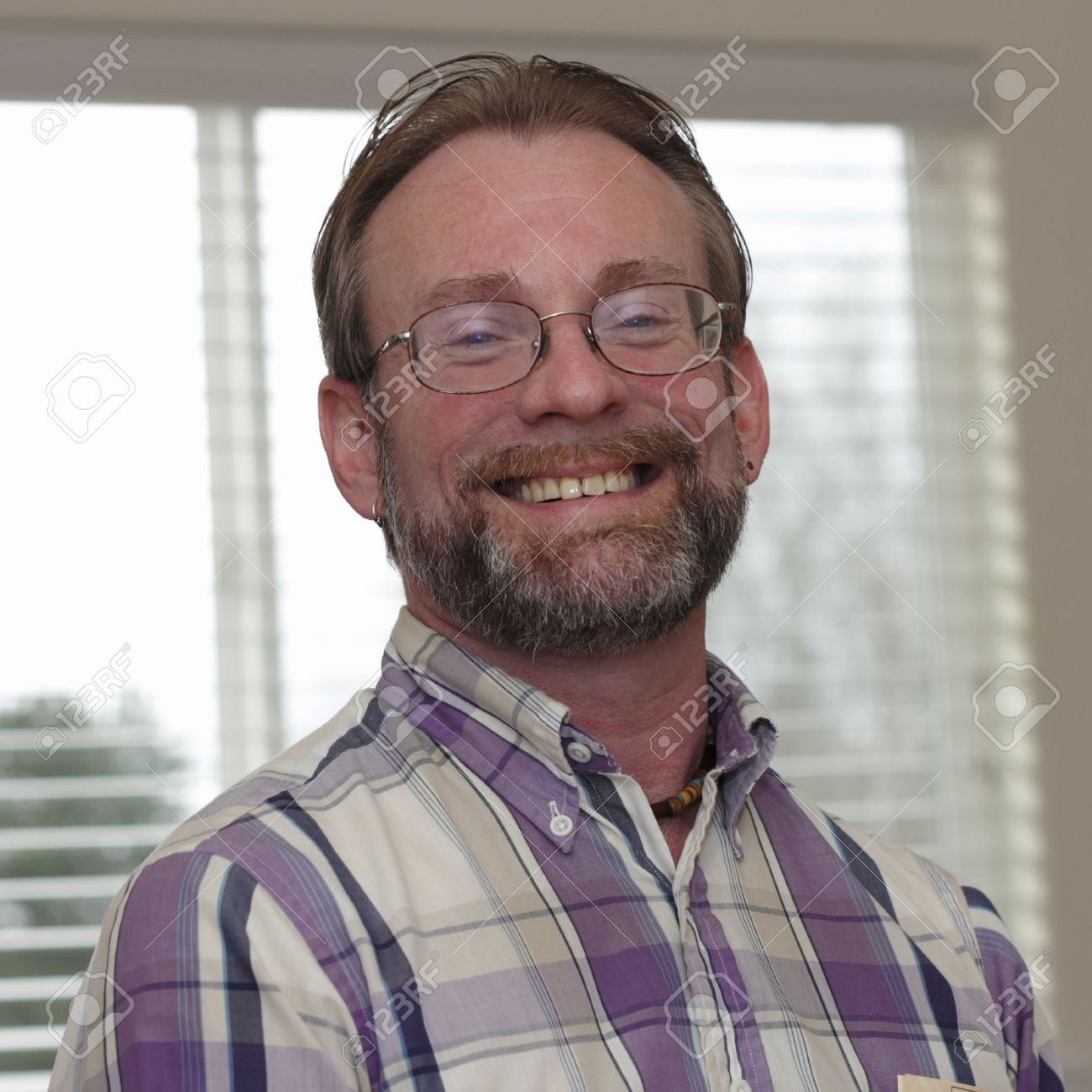 Male wearing eyeglasses in is forties with blonde gray hair and beard smiling in a joyous way showing his upper teeth Stock Photo - 14057263
