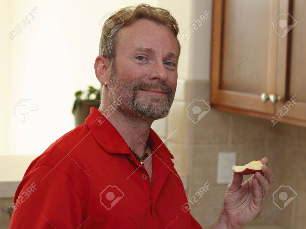 Mature man with a beard and slight smile looking at viewer while holding up an apple wedge in a kitchen. Stock Photo - 14109763