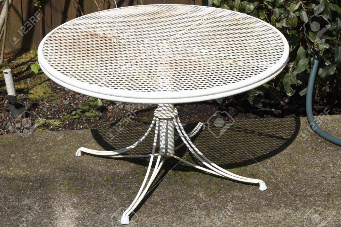 Small round metal patio table painted white aged with dirt and rust needing a good painting. Stock Photo - 14109778