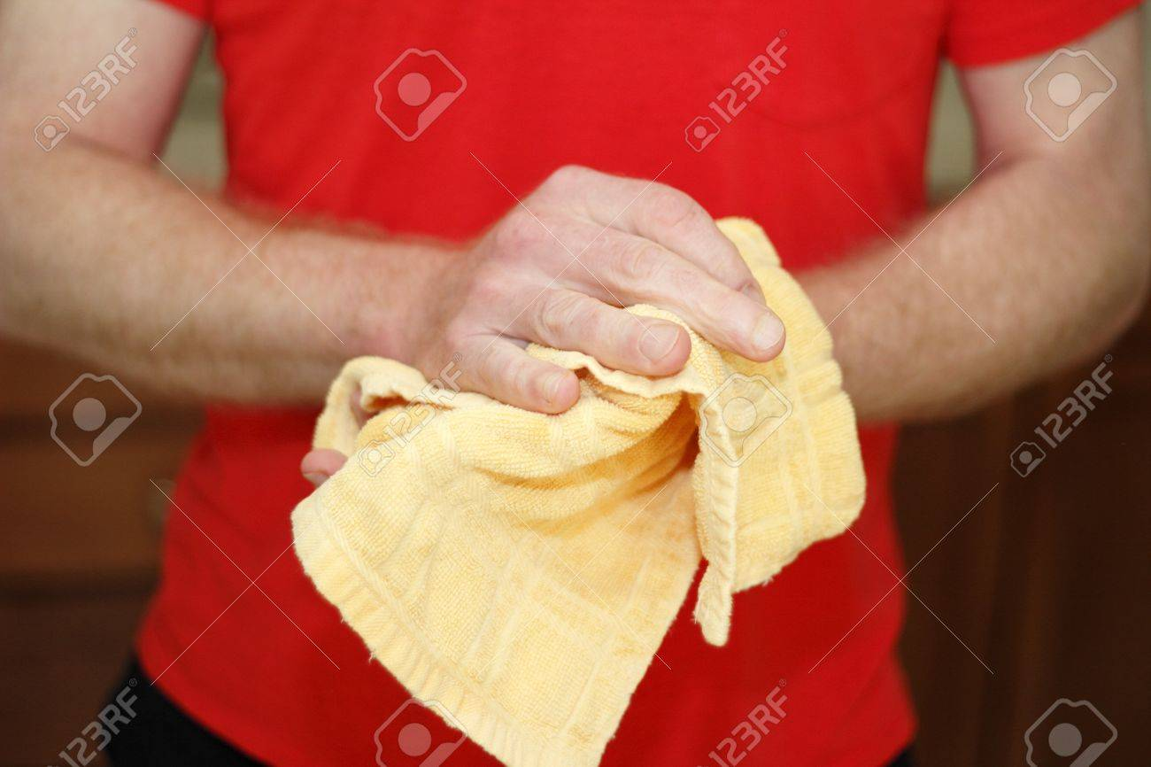 Adult male caucasian wearing a red shirt drying hands on a yellow cotton cloth dish towel close up. Stock Photo - 14373707