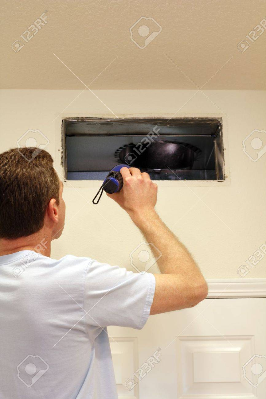 Adult male shining a flashlight into an air duct return vent to check for any need of cleaning dust or any other maintenance. Stock Photo - 14344573