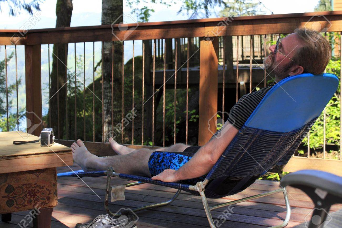 Man relaxing on a lounge chair on an outdoor deck in a forest with his eyes closed. Stock Photo - 14504149