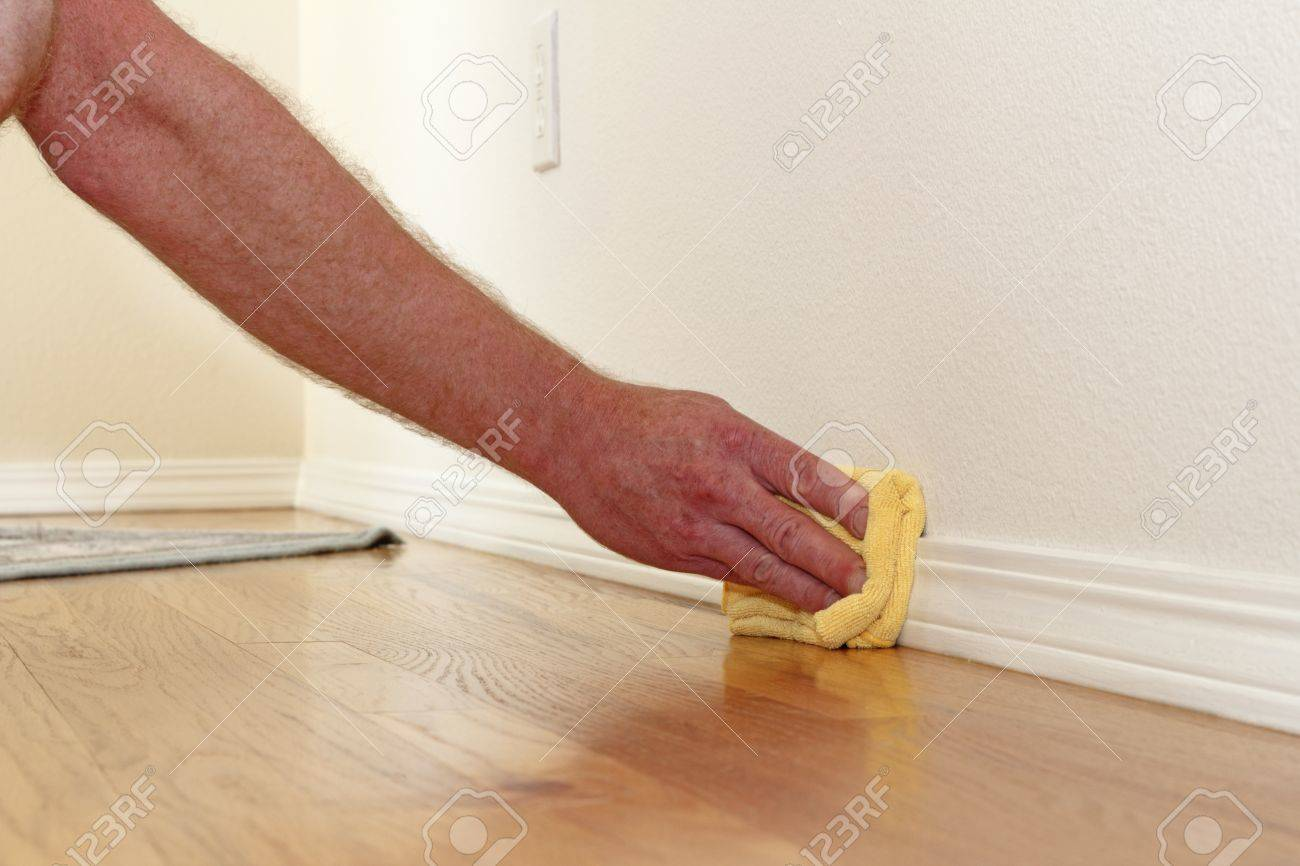 Male caucasian hand and arm seen wiping a folded yellow rag Stock Photo - 14576716