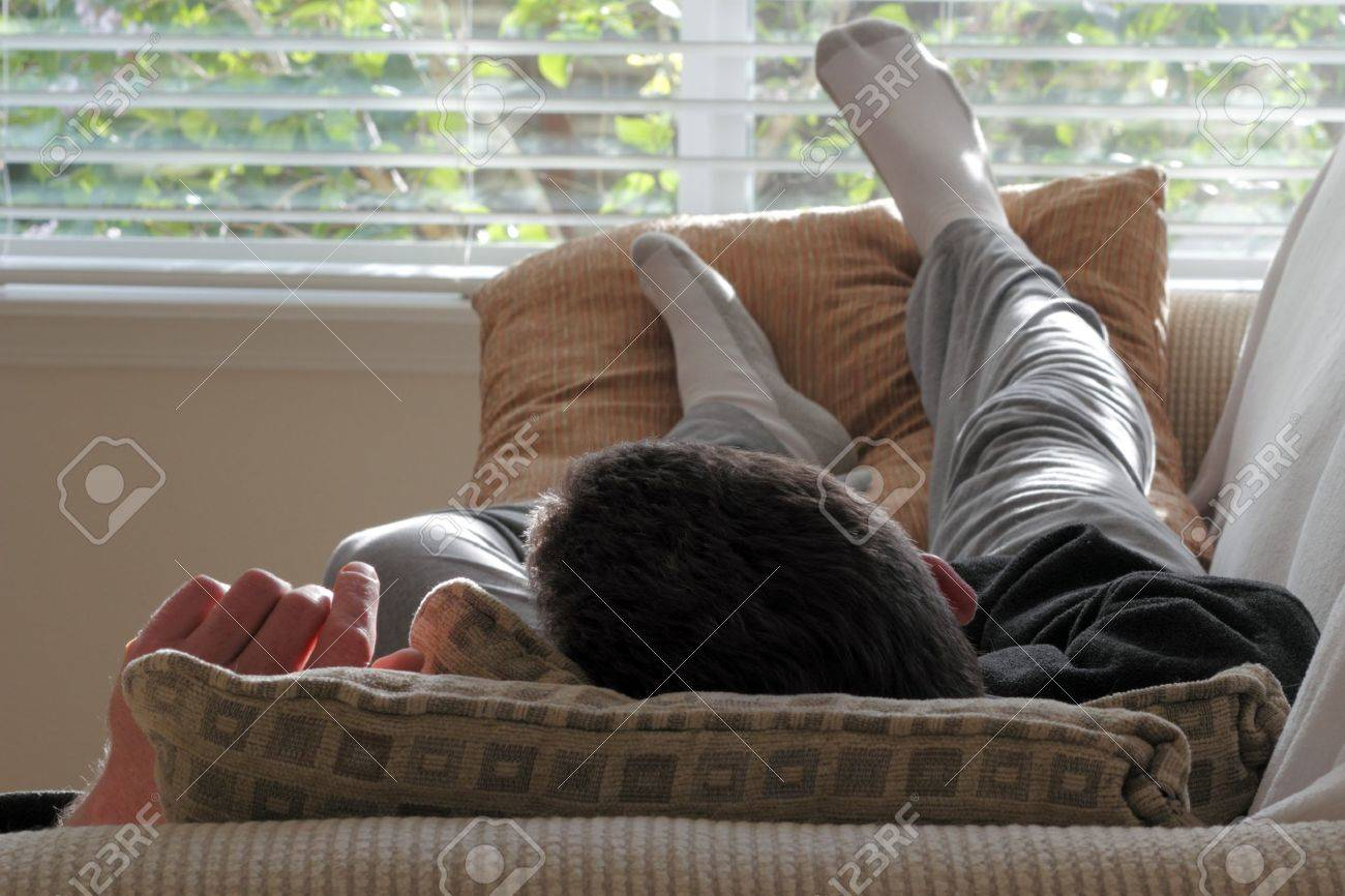 Adult caucasian male laying with his head on a pillow on a couch Stock Photo - 14649411
