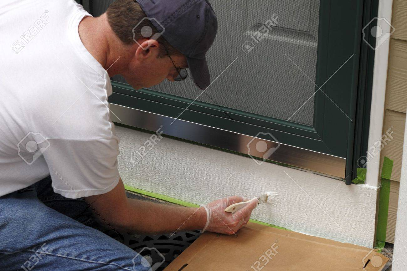 Adult male painting the white part below the front door of his home to make the entry way more inviting and better looking Stock Photo - 14707426