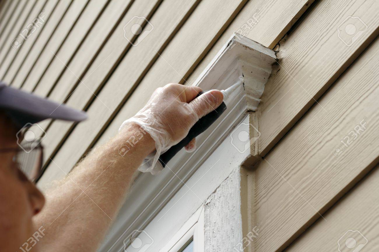 Man outdoors filling holes that developed around an exterior home window frame Stock Photo - 14707424