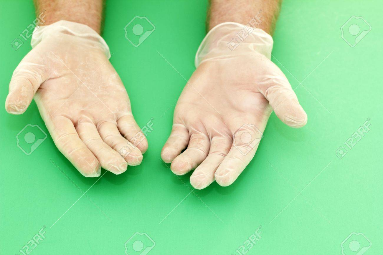 Human hands wearing powdered vinyl gloves with palms up on a green background Stock Photo - 14847885