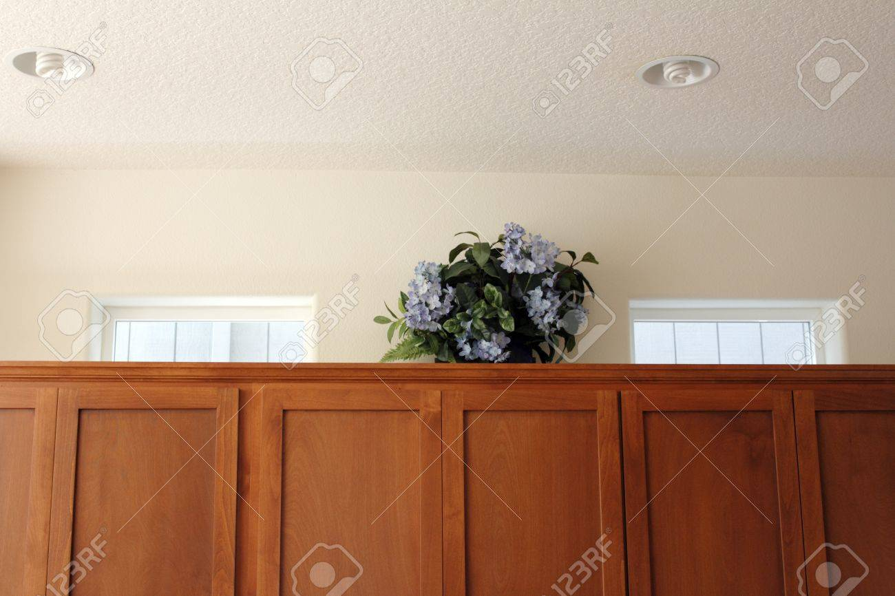 Artificial hydrangea floral arrangement in a wood basket on top of kitchen cupboards to draw the eye to the windows to help people viewing a home for sale to remember it is a detached house Stock Photo - 16431817