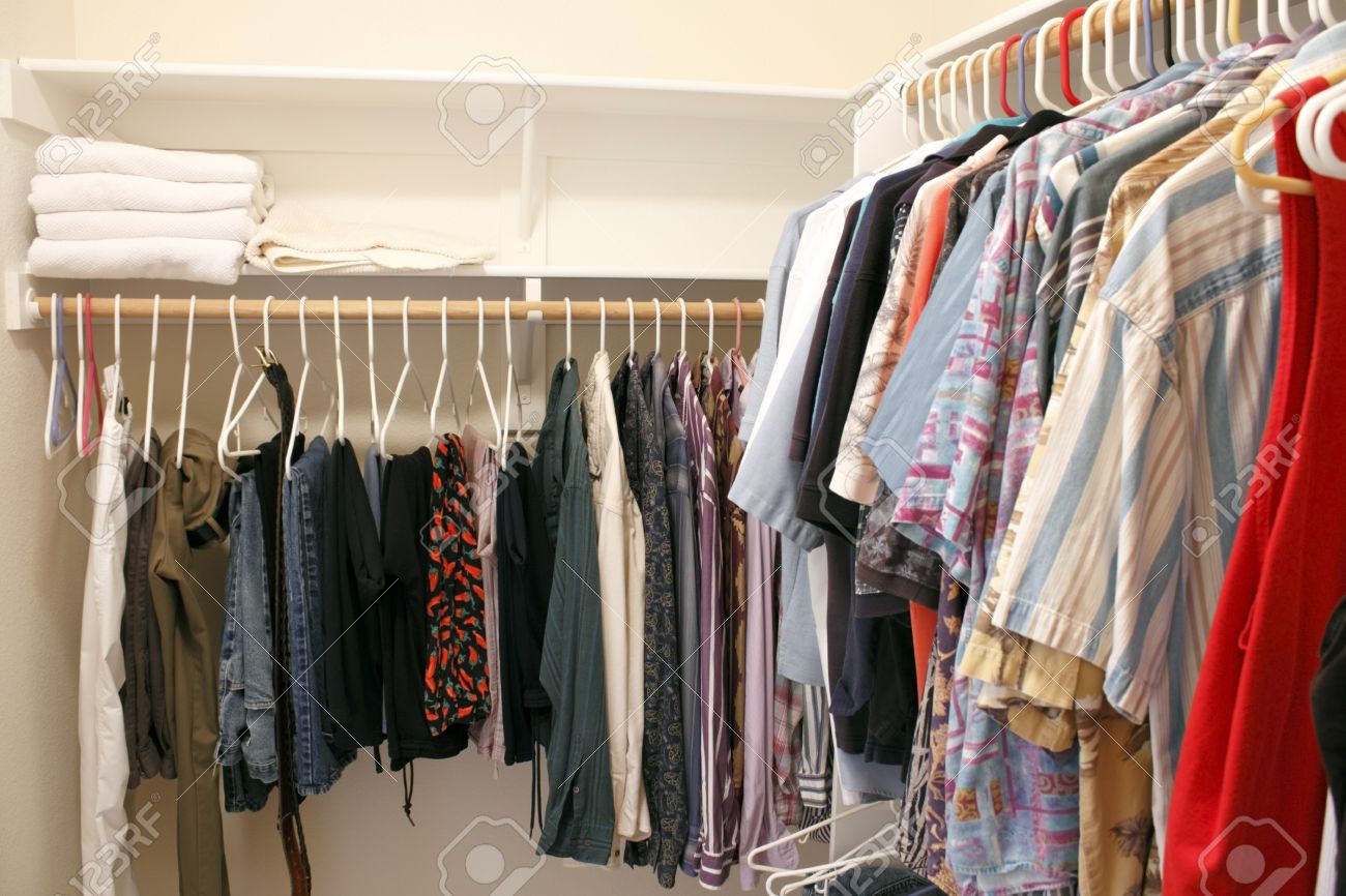 Mens wardrobe variety of pants and shirts clothing hung on plastic hangers in a home walk in closet  There are also a few bath towels on a shelf Stock Photo - 16431814