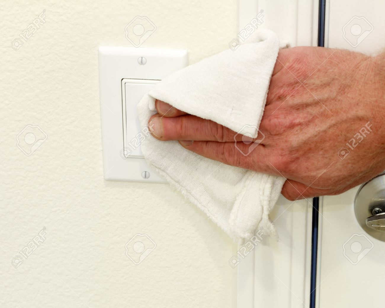 Hand Cleaning A White Home Kitchen Flat Panel Light Switch With A White  Cotton Cloth Dust