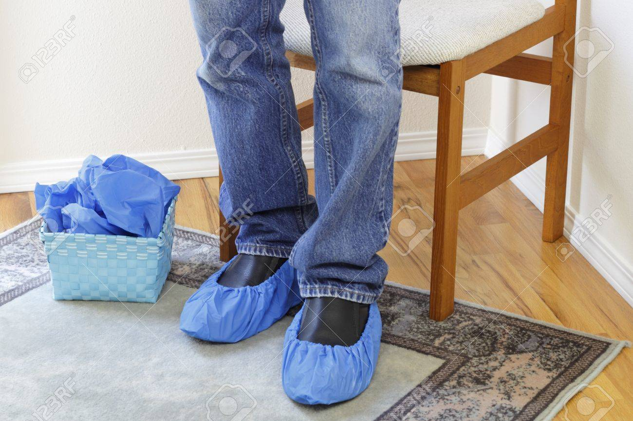 Male legs wearing jeans seen from the knees down to the floor wearing blue floor protectors called booties on both feet over a pair of black dress shoes Stock Photo - 16493830