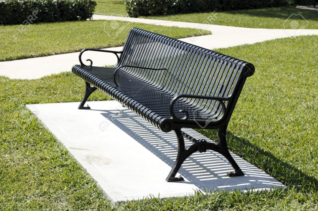 black metal two seat park bench on a concrete slab surrounded