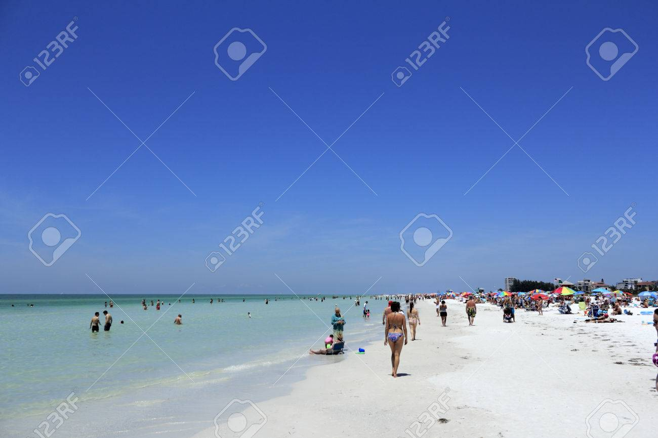 SIESTA KEY, FLORIDA - MAY 9, 2013  A colorful scene on a busy day with lots of people enjoying relaxing at the beautiful white quartz sand Siesta Beach, voted one of the best beaches in the world  Stock Photo - 25871160