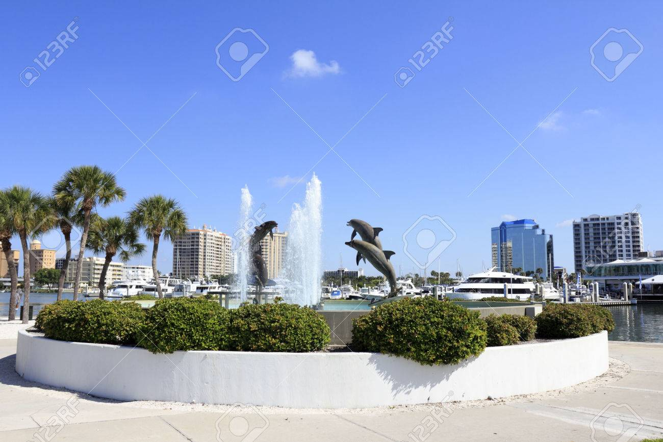 SARASOTA, FLORIDA - MAY 9, 2013: Dolphin Fountain sculpted by Steven C. Dickey, donated by Marina Jacks at the end of Sarasota Island Park and Marina with downtown buildings in the background. Stock Photo - 26089995