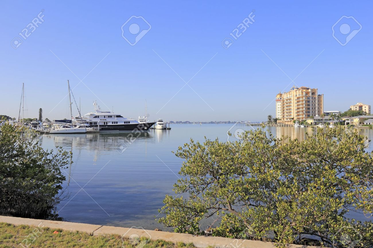 SIESTA KEY, FLORIDA - MAY 9, 2013: Beautiful view from Sarasota overlooking Sarasota bay and the gulf coast waters, docked boats, buildings and Siesta Key island in the distance on a sunny morning. Stock Photo - 26089997