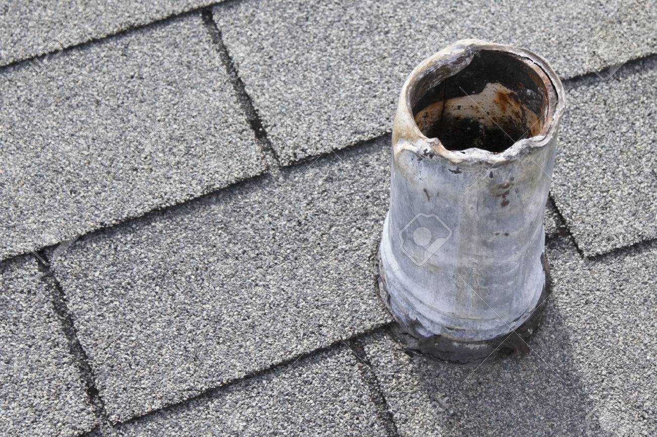 Residential short gray metal roof vent stack and black boot that shows sign of wear on top and bottom from snaking out the plumbing pipe in the past and that needs repair so there is no water damage Stock Photo - 26570811