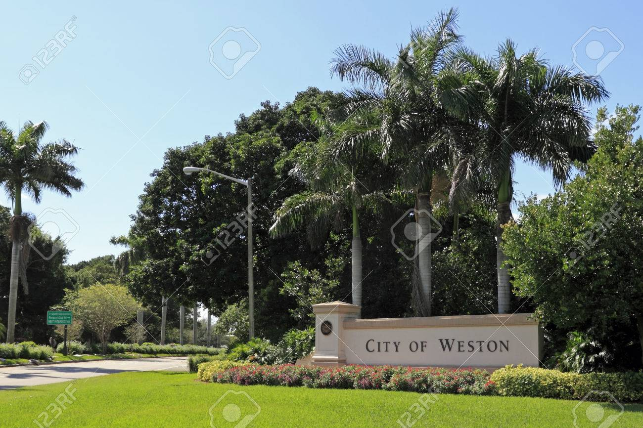 WESTON, FLORIDA - OCTOBER 22, 2013  Beautiful landscaping and flowers surround a large entrance sign to the City of Weston, located in west Broward County, population 67,641 in 2012 on a sunny day  Stock Photo - 26558066