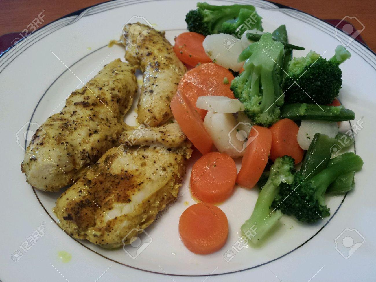 Healthy Dinner Plate Of Baked Herb Seasoned Boneless Organic Chicken Strips With Various Vegetable
