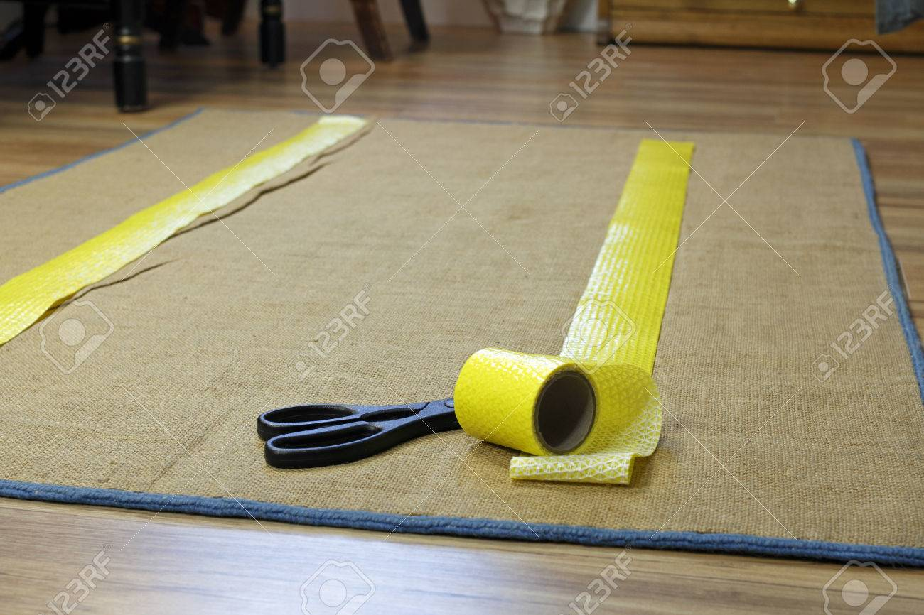 Anti-slip double sided adhesive texture tape with removable yellow plastic on one side. A roll of tape near scissors is placed on the floor rugs backing in two strips. Stock Photo - 52180020
