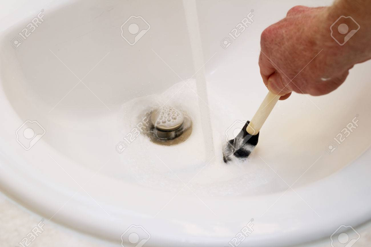 Caucasian Male Hand Cleaning White Paint From A Small Sponge Paintbrush In  A White Porcelain Sink