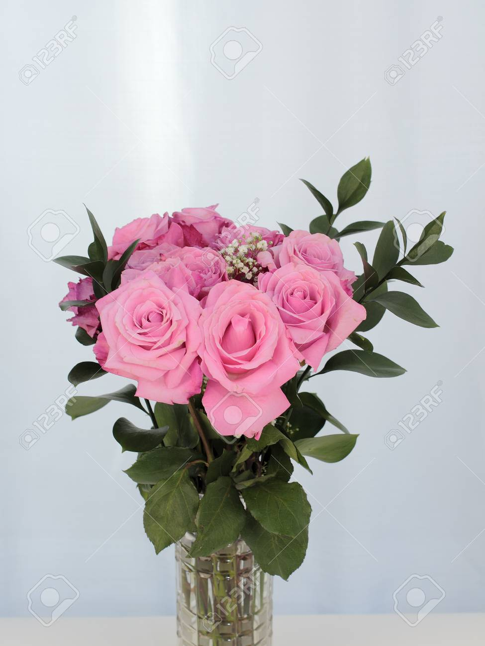 Vibrant pink rose flowers bunch in a cut glass vase with a subtle stok fotoraf vibrant pink rose flowers bunch in a cut glass vase with a subtle background green leaves and babys breath accent pink bouquet of roses in mightylinksfo