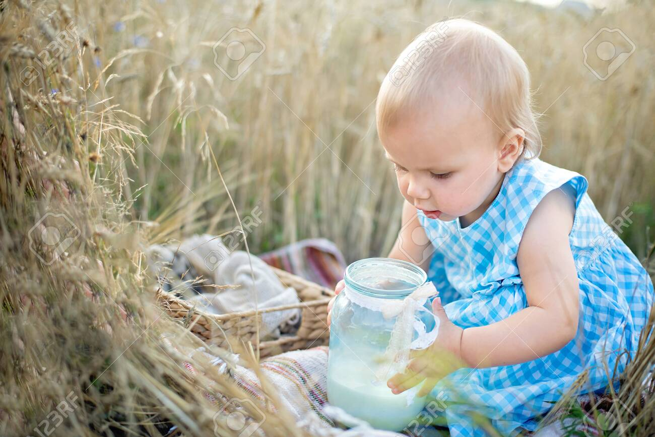 Little girl in wheat field. healthy child on picnic with bread and milk in golden cereal field. - 139109425