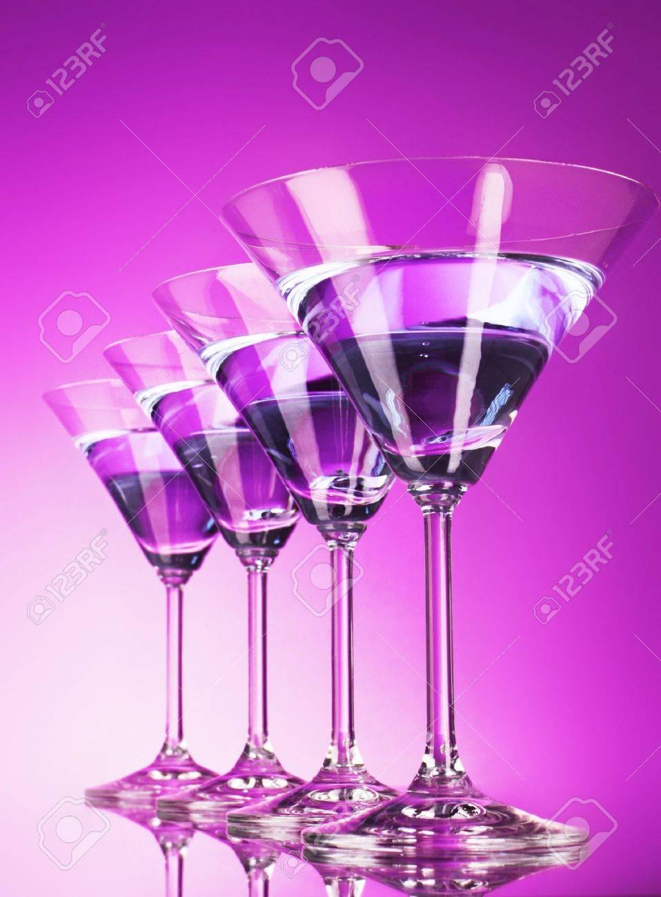 Four martini glasses on purple background Stock Photo - 8914555
