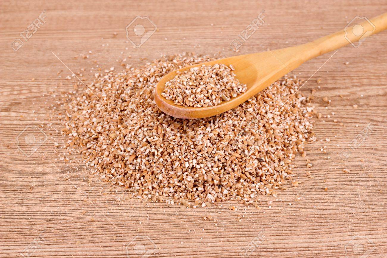 wheat grits and spoon on brown Stock Photo - 9715170