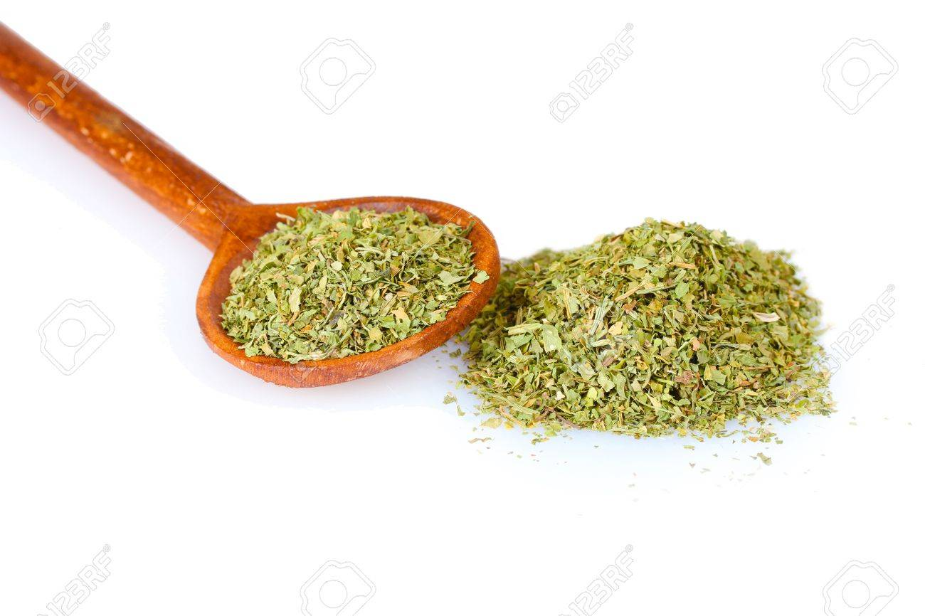 dried parsley in wooden spoon isolated on white Stock Photo - 10293487