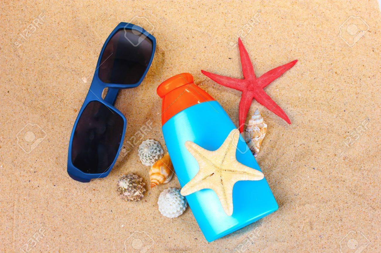 sunblock in bottle, sunglasses, shells and starfish on sand Stock Photo - 10394988