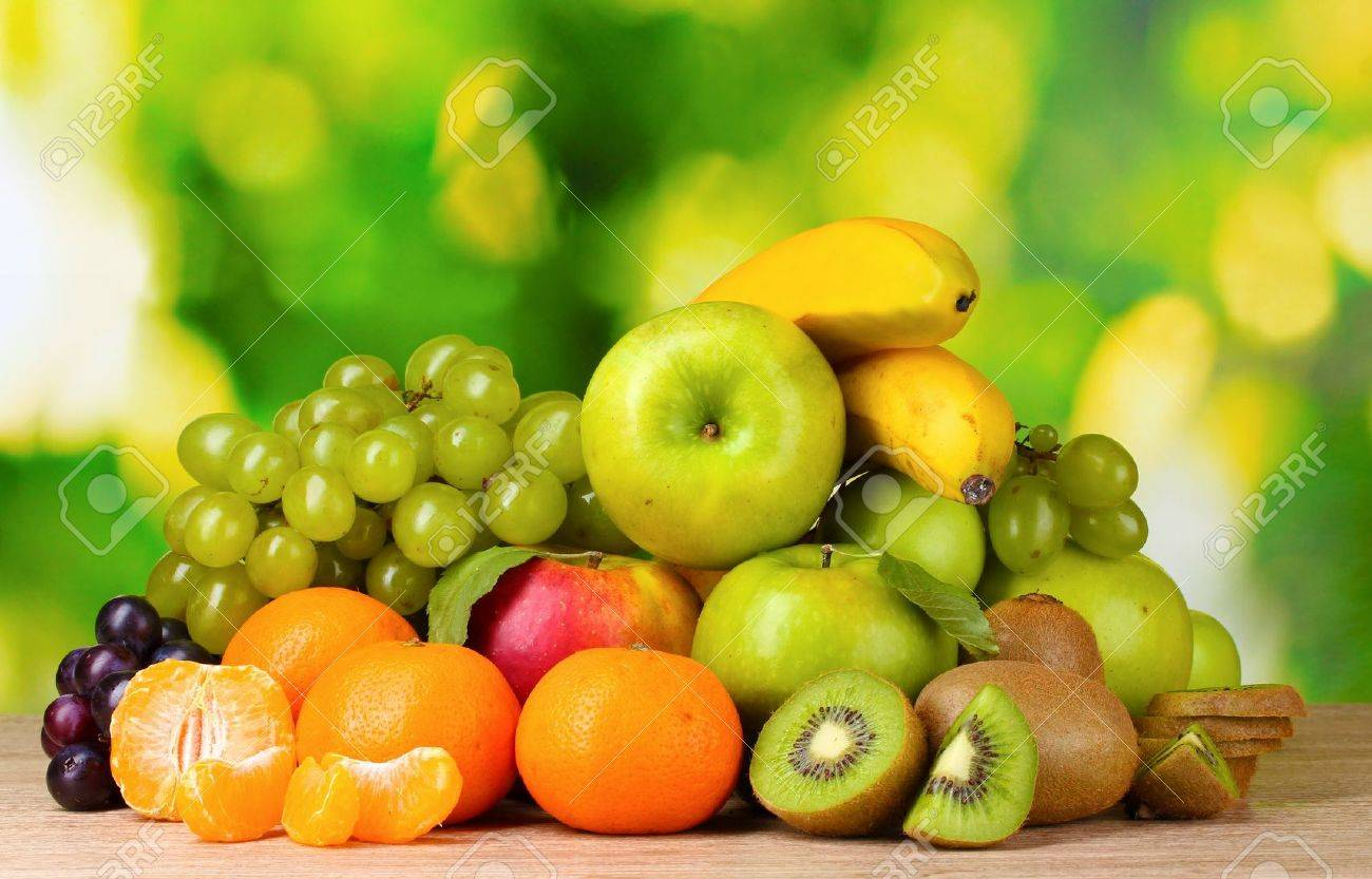 ripe juicy fruits on wooden table on green background stock photo