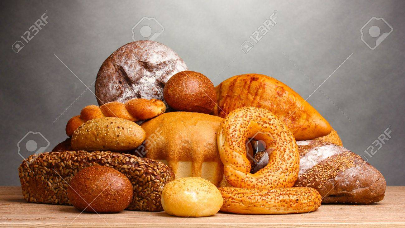 delicious bread on wooden table on gray background - 11069288