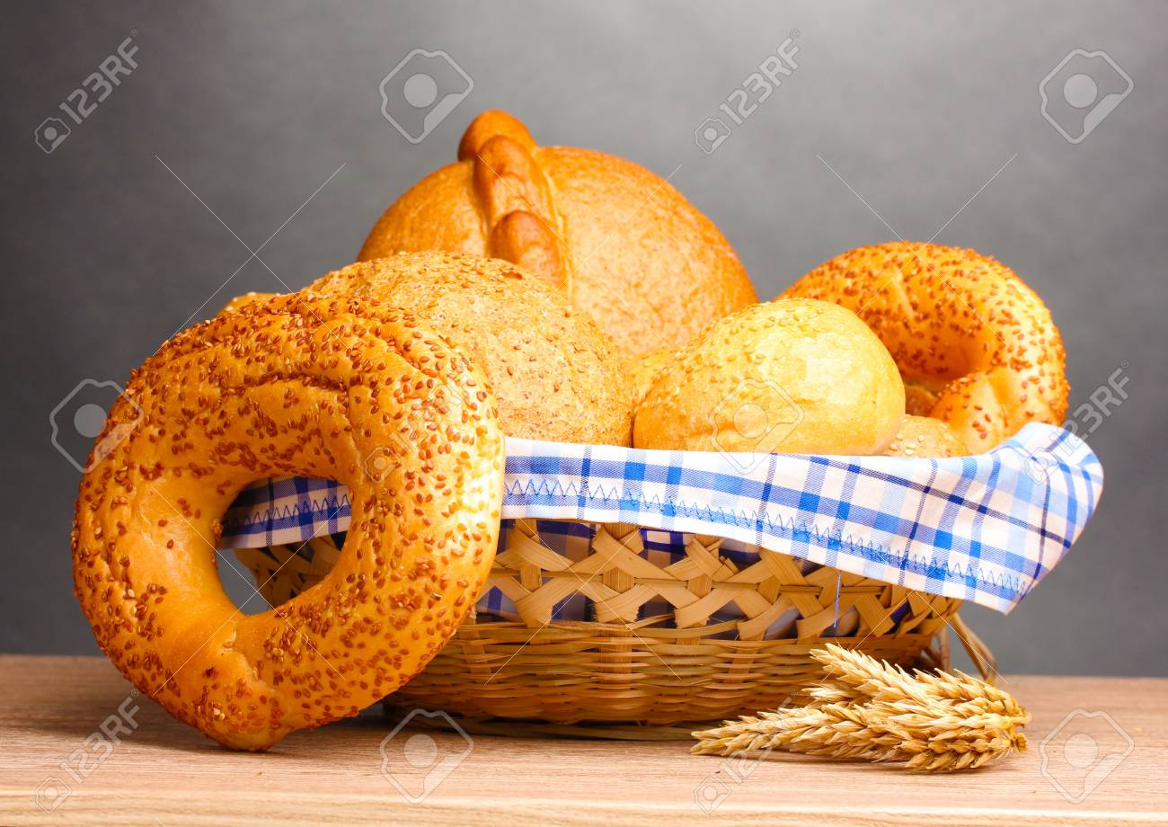 delicious bread in basket and ears on wooden table on gray background Stock Photo - 11288859