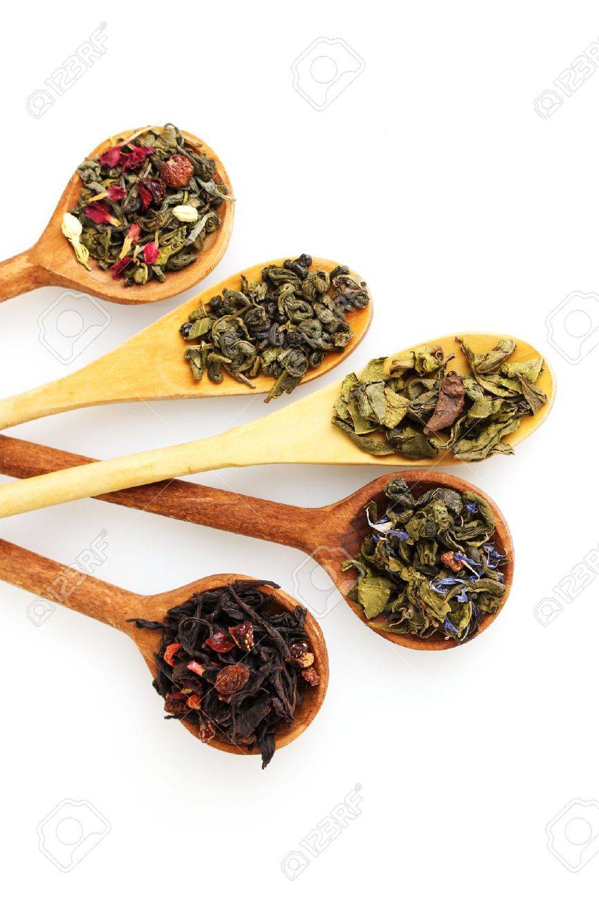 Different kinds of green and black dry tea in woooden spoon isolated on white Stock Photo - 11288693