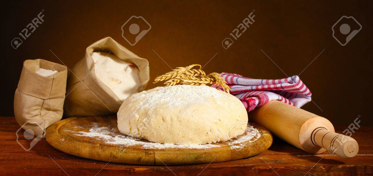 Dough and bags with flour on wooden table on brown background Stock Photo - 11399557