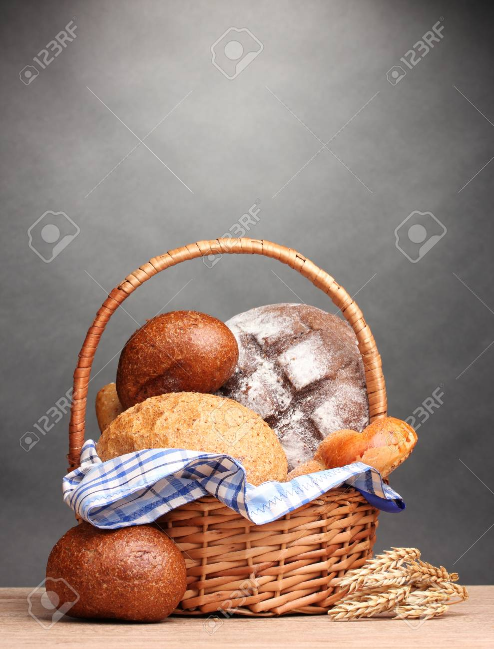 delicious bread in basket and ears on wooden table on gray background Stock Photo - 12134260
