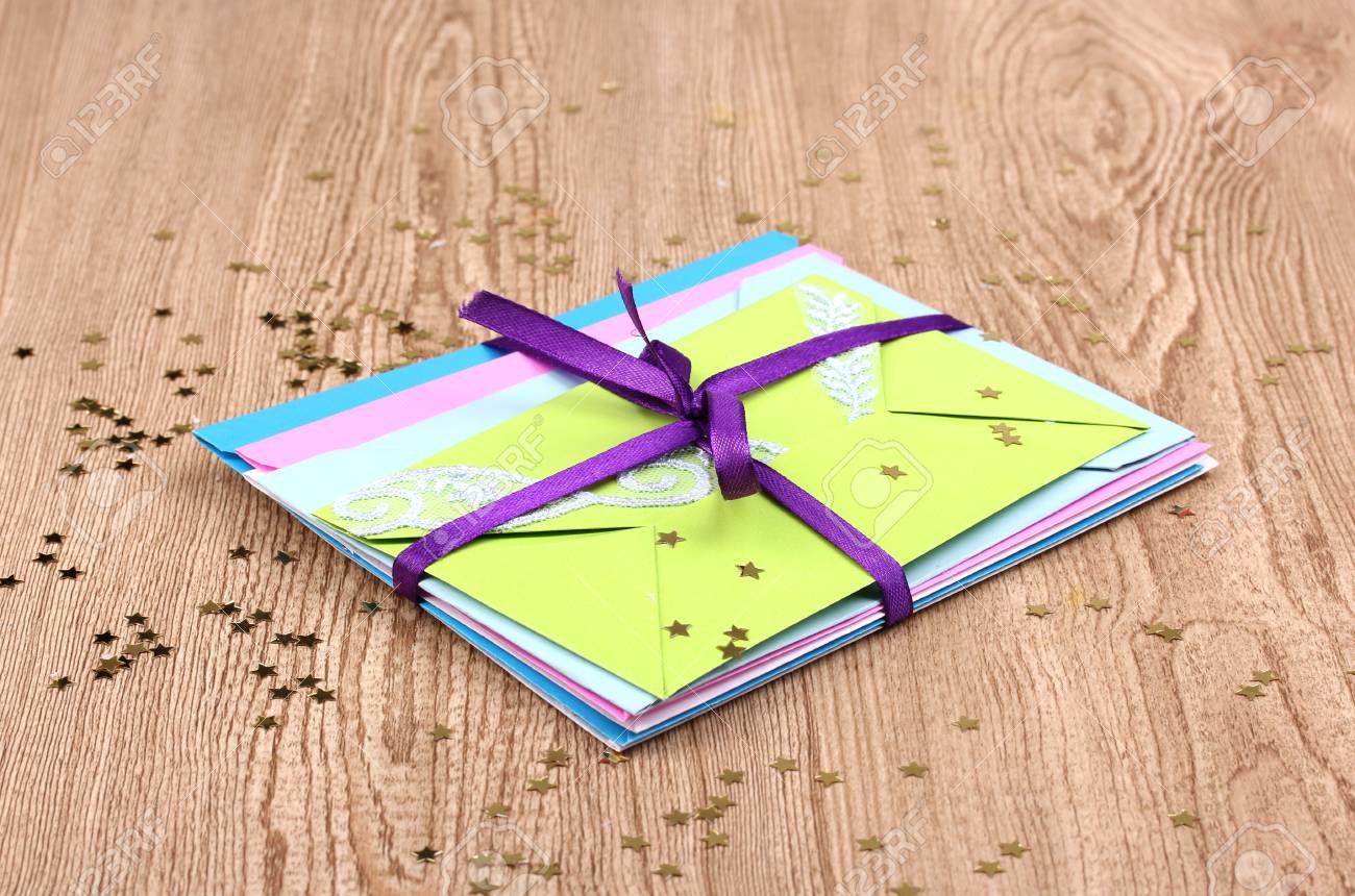 Bunch of color envelopes with ribbon and confetti on wooden background Stock Photo - 12310649